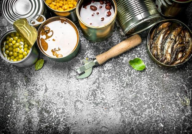 Vari cibi in scatola con carne, pesce, verdura e frutta in barattoli di latta. su fondo rustico.