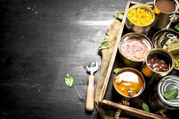 Varie conserve di frutta, verdura, pesce e carne in barattoli di latta sul vecchio vassoio.