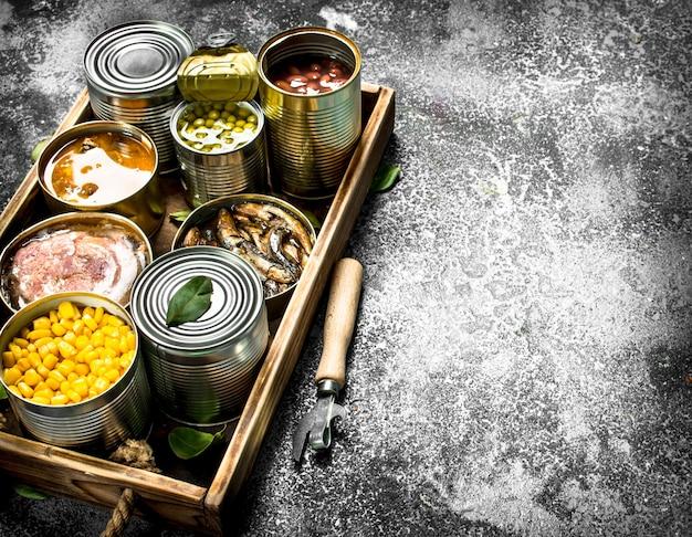 Vari prodotti in scatola in barattoli di latta su un vassoio di legno su uno sfondo rustico