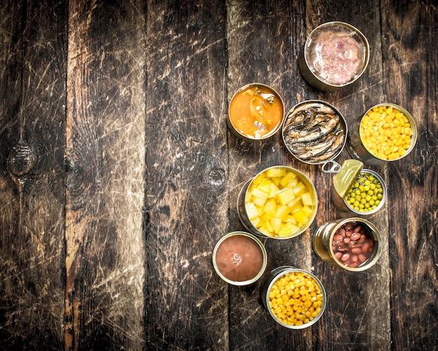 Varie verdure in scatola, carne, pesce e frutta in barattoli di latta su uno sfondo di legno
