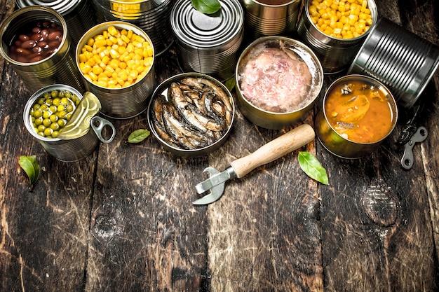 Varie verdure in scatola, carne, pesce e frutta in barattoli di latta. su uno sfondo di legno.