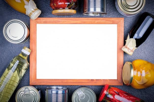 Varie conserve vegetali, carne, pesce e frutta in scatola e vetro con bordo.