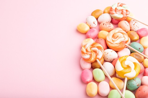 Varie caramelle al caramello su pastello rosa