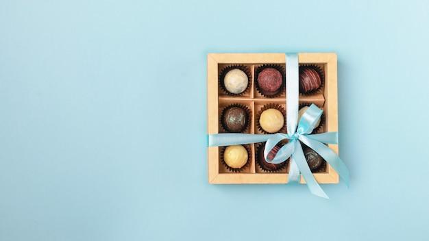 Vari cioccolatini in scatola di carta artigianale con un nastro blu satinato su un blu brillante