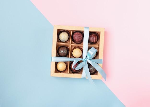 Vari cioccolatini in scatola di carta artigianale con un nastro blu satinato su colori vivaci