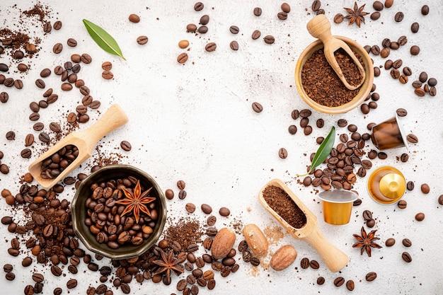 Caffè vari, chicchi di caffè tostati scuri, macinato e capsule con palette installate su cemento bianco