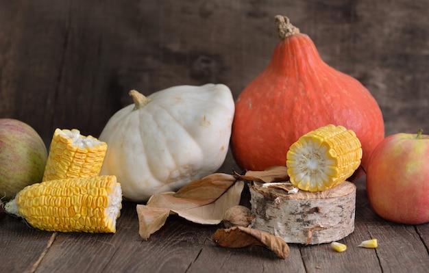 Varie e colorate verdure autunnali e frutta e pannocchia di mais tagliata a pezzi su fondo in legno