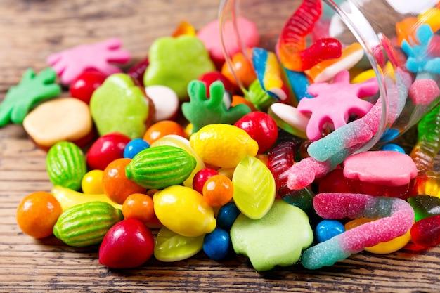 Varie caramelle colorate, gelatine e marmellate in un barattolo di vetro sulla tavola di legno