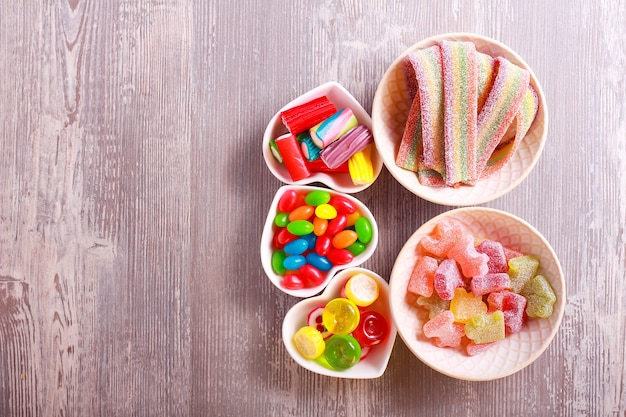 Varie caramelle colorate in piastre su sfondo di legno
