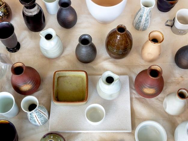 Vari vasi in ceramica colorati disposti su tessuto di calicò bianco, vista dall'alto. vaso di ceramica vuoto.