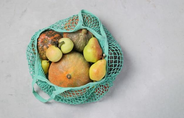 Varie zucche colorate, pere e mele in sacchetto di maglia a rete turchese su sfondo chiaro, concetto di rifiuti zero, spazio di copia, vista dall'alto.