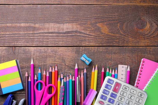 Varie forniture scolastiche colorate su un tavolo di legno marrone.