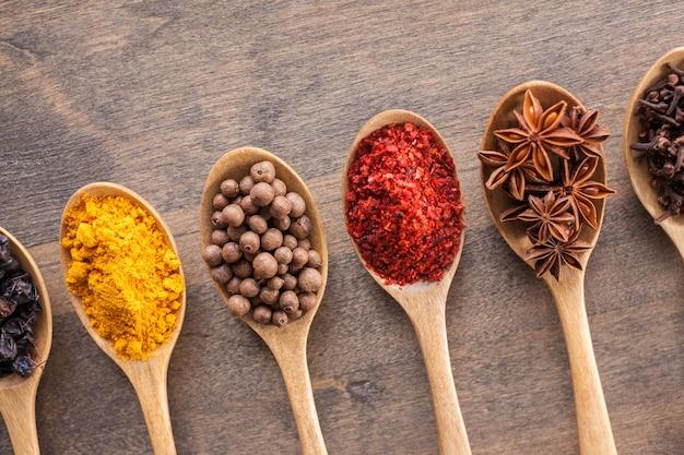 Varie spezie colorate in cucchiai sul tavolo di legno