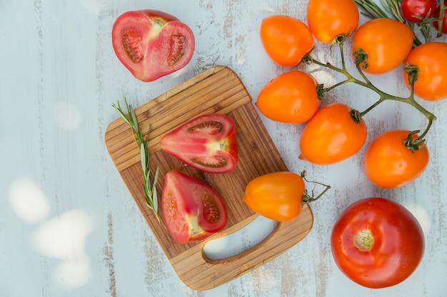 Vari pomodori colorati ed erbe di rosmarino su una superficie azzurra