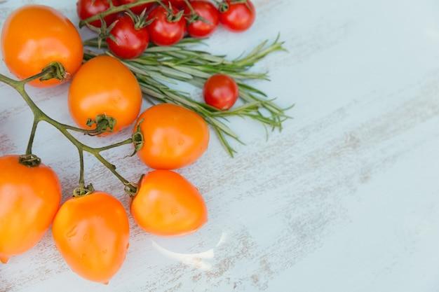 Vari pomodori colorati ed erbe di rosmarino su azzurro