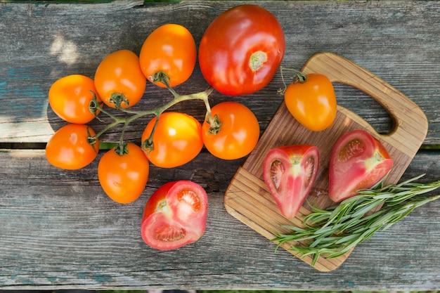 Vari pomodori colorati e rosmarino erba sul vecchio fondo di legno rustico