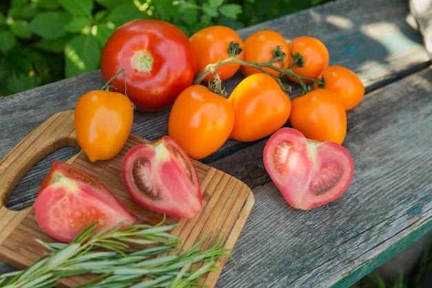 Vari pomodori colorati e rosmarino erba sul vecchio tavolo in legno