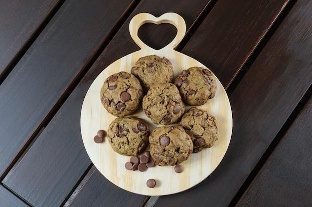 Vari biscotti su una tavola di legno. accanto a gocce di cioccolatini. vista dall'alto.