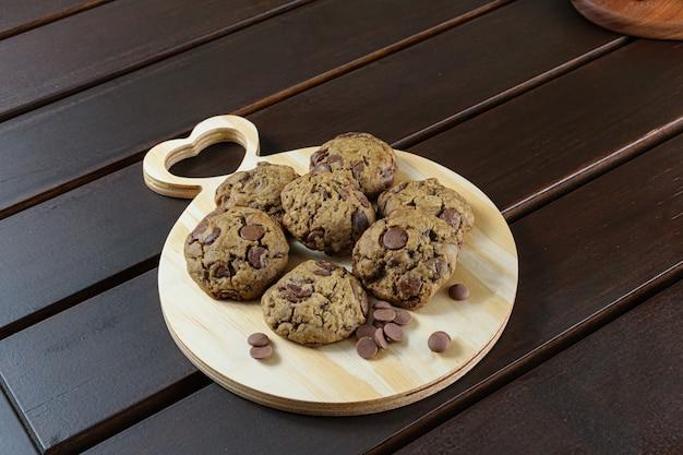 Vari biscotti su una tavola di legno. accanto a gocce di cioccolatini.