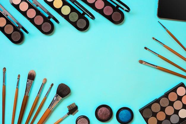 Vari cosmetici e pennelli su sfondo blu