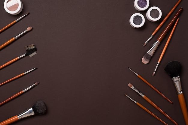 Vari cosmetici e pennelli su sfondo marrone