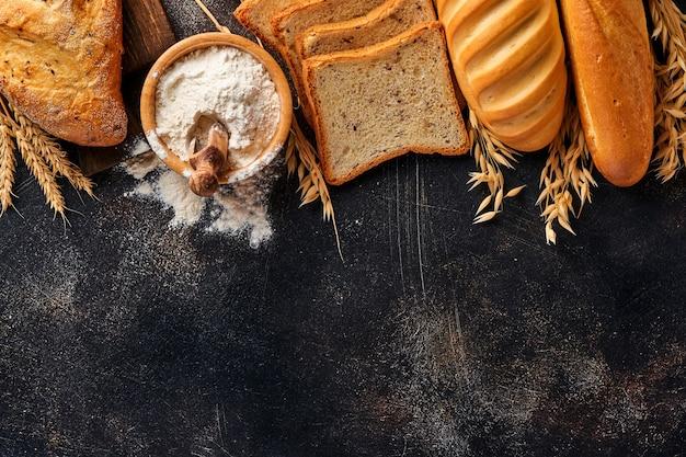 Vari pani e focacce croccanti, farina di frumento e spighe sul vecchio tavolo in cemento grigio.