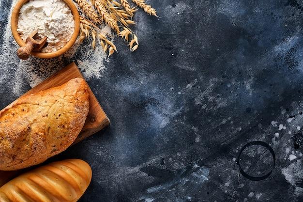 Vari pani e focacce croccanti, farina di frumento e spighe sul vecchio tavolo di cemento grigio