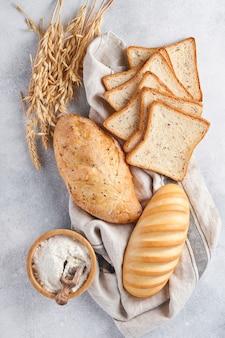 Vari tipi di pane e focacce croccanti, farina di frumento e spighe sul tavolo di fondo in cemento grigio chiaro