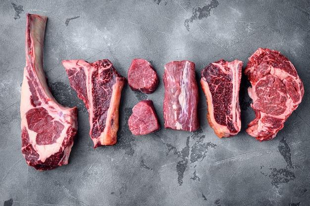 Vari tagli di carne di manzo marmorizzata e set di bistecche stagionate a secco, tomahawk, t bone, club steak, rib eye e tagli di filetto su pietra grigia