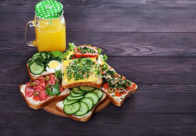 Vari deliziosi panini con salmone, germogli, pomodori, cetrioli, erbe aromatiche, noci, olive e succo d'arancia fresco