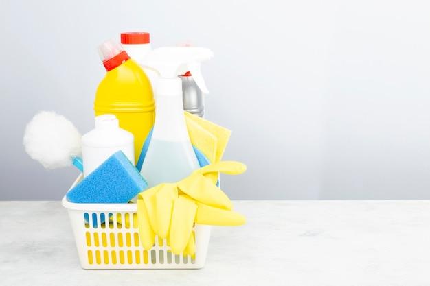 Vari detergenti e prodotti per la pulizia agente, spugne, tovaglioli e guanti di gomma, sfondo grigio. copia spazio