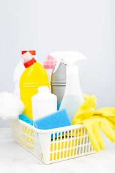 Vari detergenti e prodotti per la pulizia agente, spugne, tovaglioli e guanti di gomma, sfondo grigio