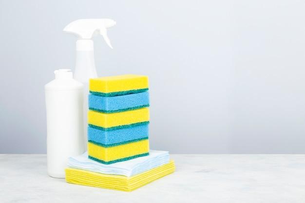 Vari prodotti detergenti agente, pila di spugne e tovaglioli per la pulizia, sfondo grigio. copia spazio