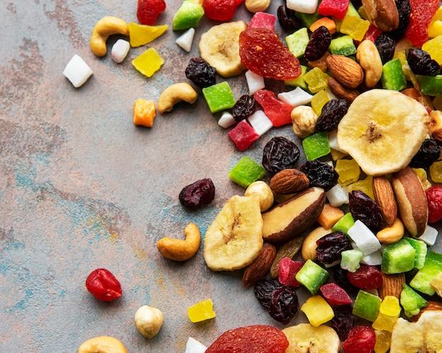 Vari frutti secchi e noci miste su una superficie di cemento grigio
