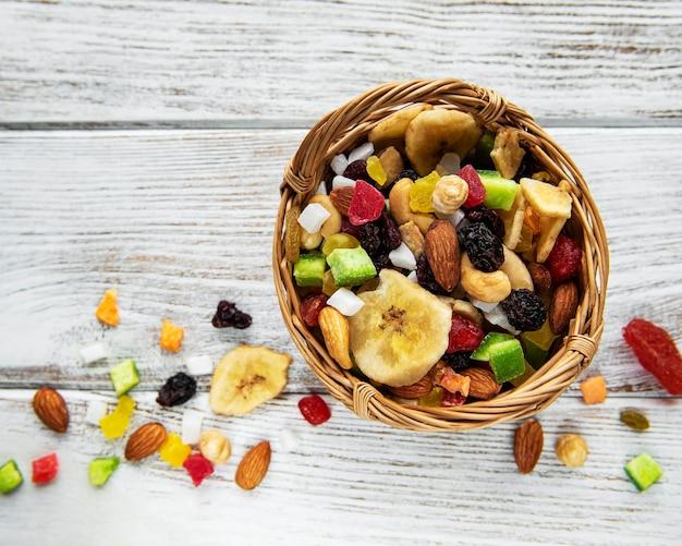 Vari frutti secchi e noci della miscela su un fondo di legno bianco.