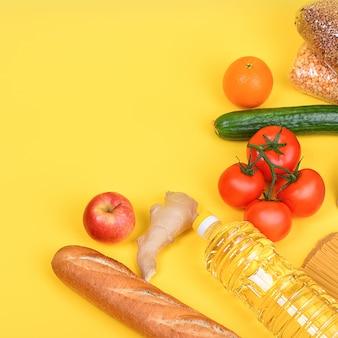 Vari prodotti alimentari, frutta e verdura su un giallo