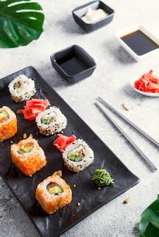 Vari sushi fresco e delizioso impostato su ardesia in bianco e nero con bastoncini di metallo e ardesia, salsa e foglie verdi sulla superficie della pietra chiara