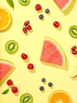 Varie frutta fresca e bacche su sfondo giallo, vista dall'alto