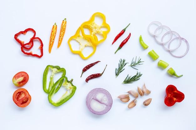 Varie verdure fresche ed erbe aromatiche sulla parete bianca. concetto di mangiare sano