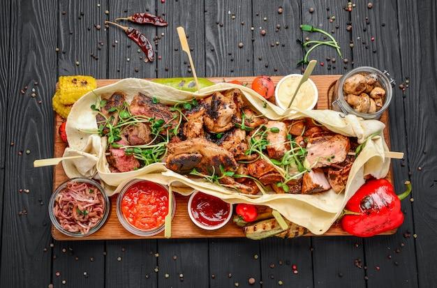Vari snack di carne alla griglia fritti con varie salse Foto Premium