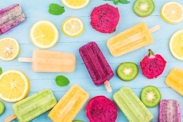 Vari ghiaccioli alla frutta sono posizionati sullo sfondo blu della tavola di legno, ghiaccioli kiwi, ghiaccioli arancioni, ghiaccioli frutta drago, ghiaccioli melone