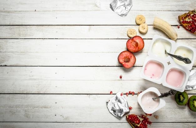Vari yogurt alla frutta. su un tavolo di legno bianco.