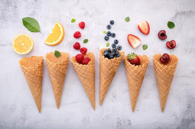 Vari di frutti in configurazione coni su sfondo di pietra bianca.
