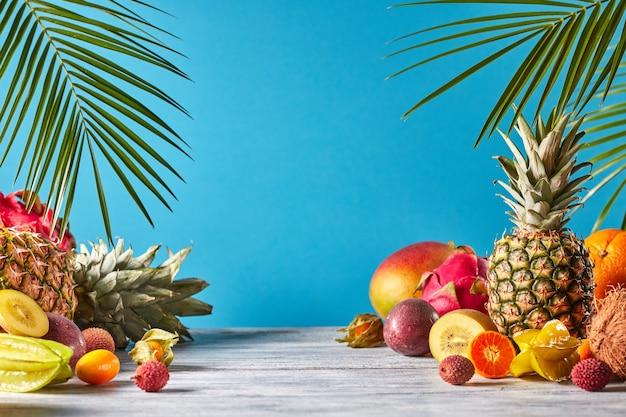 Vari frutti foglia di palma esotica su un tavolo di legno grigio
