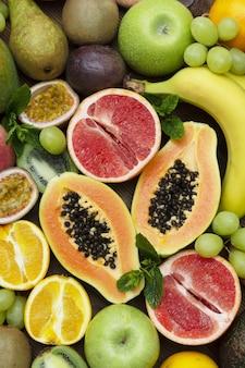 Vari frutti si mescolano su fondo in legno. concetto di estate. lay piatto.