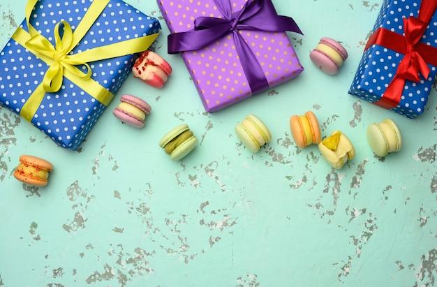 Varie scatole regalo con fiocchi legati e pasta al forno su sfondo verde, vista dall'alto