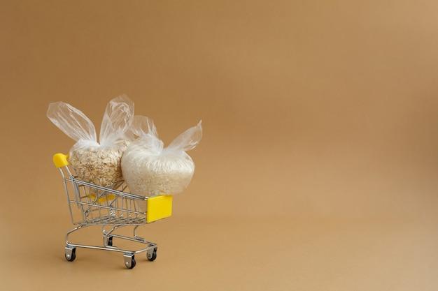 Vari semole in pacchetti in un carrello della spesa su uno sfondo marrone. riso e farina d'avena