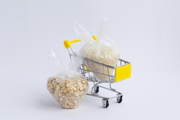 Vari semole in confezioni in un carrello della spesa su uno sfondo bianco. riso e farina d'avena