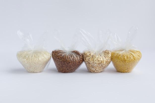 Vari semole in piccoli sacchetti di plastica su uno sfondo bianco. riso e farina d'avena, grano saraceno e miglio