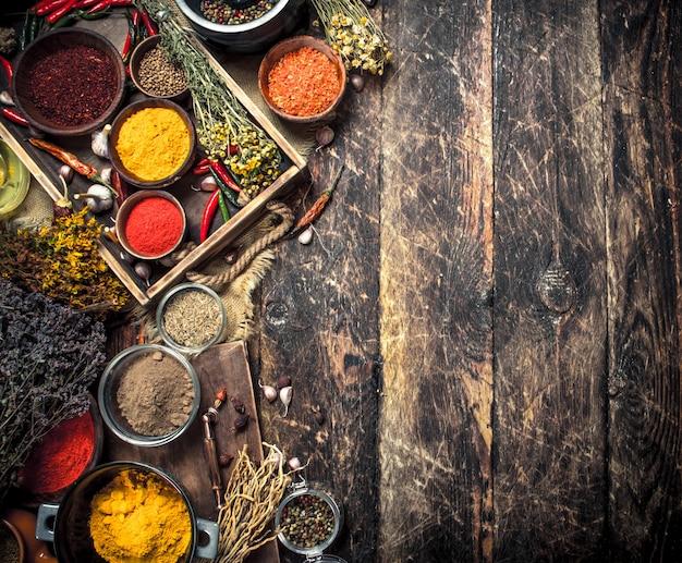 Varie spezie ed erbe aromatiche macinate in un vecchio vassoio. su uno sfondo di legno.
